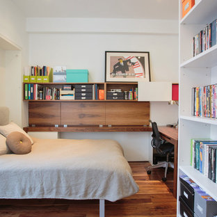 Small trendy guest medium tone wood floor and brown floor bedroom photo in New York with white walls and no fireplace