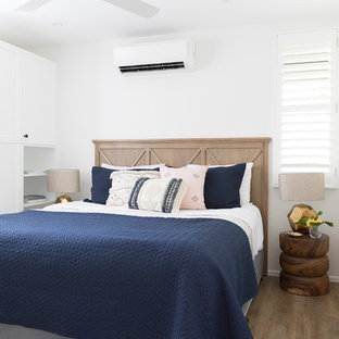Photo of a contemporary bedroom in Brisbane with white walls and light hardwood floors.