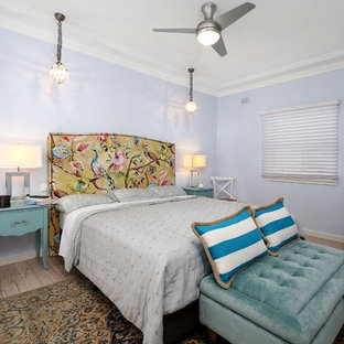 Traditional bedroom in Sydney with blue walls and light hardwood floors.