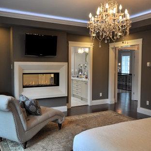 Immagine di una grande camera matrimoniale con pareti grigie, parquet scuro, camino bifacciale, cornice del camino in intonaco e pavimento marrone