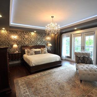 大きいおしゃれな主寝室 (グレーの壁、濃色無垢フローリング、両方向型暖炉、漆喰の暖炉まわり、茶色い床) のインテリア