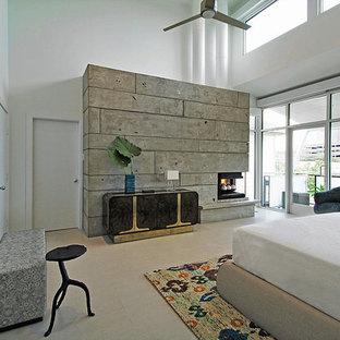 Immagine di una grande camera matrimoniale design con pareti bianche, camino ad angolo, cornice del camino in cemento, pavimento con piastrelle in ceramica e pavimento beige