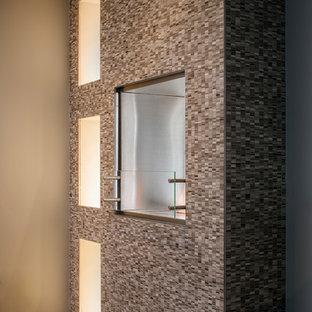 Imagen de dormitorio principal, contemporáneo, pequeño, con paredes grises, suelo de madera clara, chimenea de doble cara, marco de chimenea de piedra y suelo marrón