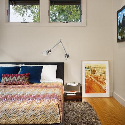 Bedroom - modern master medium tone wood floor bedroom idea in Austin with beige walls