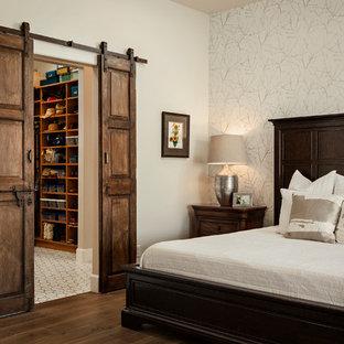 Imagen de dormitorio principal, de estilo americano, de tamaño medio, con paredes beige, suelo de baldosas de cerámica y suelo marrón