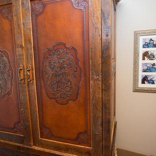 Ejemplo de habitación de invitados de estilo americano, grande, con parades naranjas, suelo de madera oscura y suelo marrón