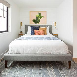 Foto de habitación de invitados nórdica, pequeña, sin chimenea, con paredes blancas, suelo laminado y suelo marrón