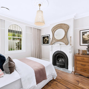 Design ideas for a transitional bedroom in Sydney with beige walls, medium hardwood floors, a standard fireplace and brown floor.