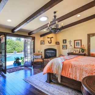 ロサンゼルスの大きい地中海スタイルのおしゃれな主寝室 (ベージュの壁、濃色無垢フローリング、コーナー設置型暖炉、漆喰の暖炉まわり、茶色い床)