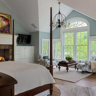 Foto de dormitorio principal, tradicional, grande, con paredes azules, chimenea tradicional, suelo de madera clara y marco de chimenea de piedra