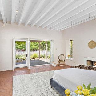Modelo de dormitorio principal, de estilo americano, grande, con paredes beige, suelo de ladrillo, chimenea tradicional, marco de chimenea de ladrillo y suelo naranja