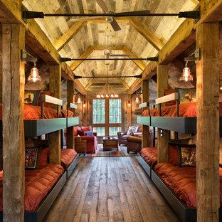 Exemple d'une très grande chambre d'amis montagne avec un mur marron et un sol en bois brun.