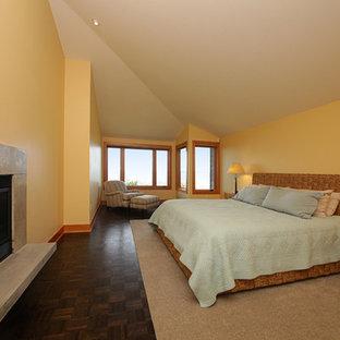 Idéer för att renovera ett funkis huvudsovrum, med gula väggar, mörkt trägolv, en standard öppen spis och en spiselkrans i betong