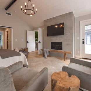 シアトルの小さいコンテンポラリースタイルのおしゃれな主寝室 (グレーの壁、淡色無垢フローリング、茶色い床、標準型暖炉、漆喰の暖炉まわり)