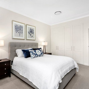 This is an example of a transitional master bedroom in Sydney with beige walls, carpet and grey floor.
