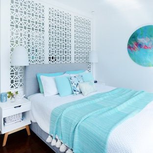 Photo of a mid-sized beach style master bedroom in Sydney with white walls, no fireplace, brown floor and dark hardwood floors.