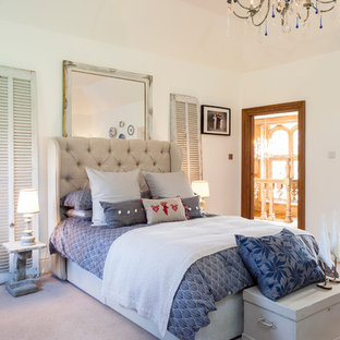 Elegant carpeted bedroom photo in London with white walls