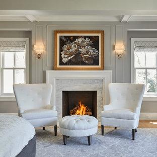 シカゴの中くらいのカントリー風おしゃれな主寝室 (グレーの壁、淡色無垢フローリング、標準型暖炉、木材の暖炉まわり、ベージュの床、格子天井、パネル壁) のレイアウト