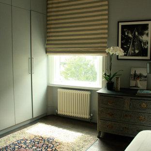 Foto de dormitorio principal, de tamaño medio, con paredes verdes, suelo de madera oscura y suelo verde