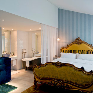 Example of a trendy master bedroom design in London with blue walls