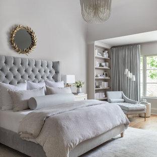 Großes Klassisches Hauptschlafzimmer mit grauer Wandfarbe, braunem Holzboden, Kamin, Kaminumrandung aus Stein und braunem Boden in Houston