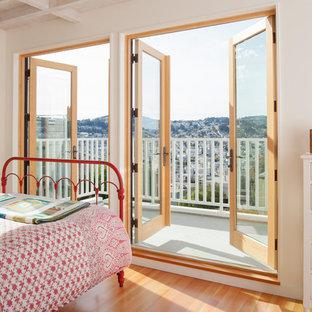 Idéer för ett minimalistiskt sovrum, med vita väggar, mellanmörkt trägolv och brunt golv