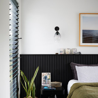 Inspiration for a mid-sized contemporary master bedroom in Other with white walls, concrete floors, black floor and decorative wall panelling.