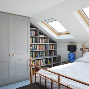 This is an example of a small traditional bedroom in London with white walls and blue floors.