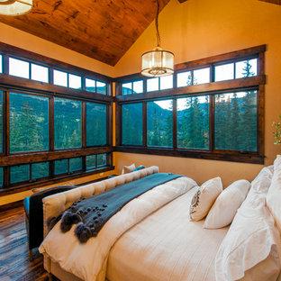 Diseño de dormitorio principal, rústico, de tamaño medio, sin chimenea, con paredes amarillas, suelo de madera oscura y suelo marrón