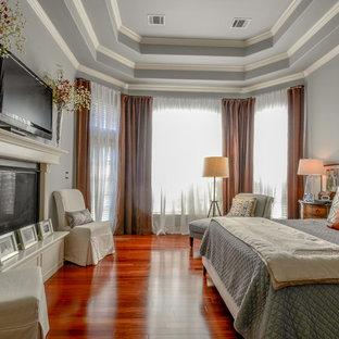 Klassisk inredning av ett huvudsovrum, med grå väggar, mellanmörkt trägolv, en standard öppen spis och orange golv