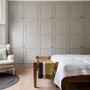 Diseño de dormitorio principal, clásico renovado, grande, con paredes grises y suelo de madera clara