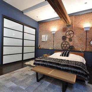 Ejemplo de dormitorio tipo loft, urbano, de tamaño medio, sin chimenea, con suelo de madera oscura, paredes azules y suelo marrón