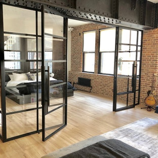 Inspiration for a mid-sized industrial loft-style bedroom in New York with multi-coloured walls, light hardwood floors and beige floor.