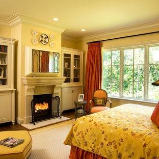 Imagen de dormitorio principal, de estilo americano, grande, con paredes beige, suelo de madera en tonos medios, chimenea tradicional y marco de chimenea de piedra