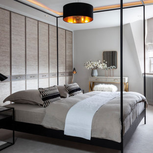 Medium sized contemporary master bedroom in London with grey walls, carpet and grey floors.