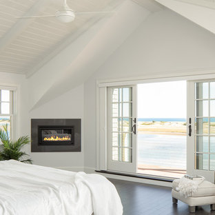 This is an example of a large beach style master bedroom in Portland Maine with white walls, dark hardwood floors, a ribbon fireplace and a tile fireplace surround.