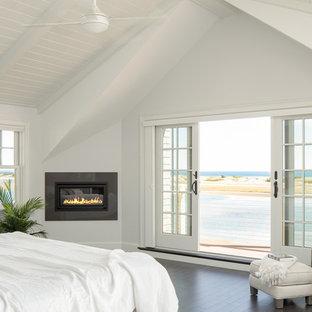Стильный дизайн: большая хозяйская спальня в морском стиле с белыми стенами, темным паркетным полом, горизонтальным камином и фасадом камина из плитки - последний тренд