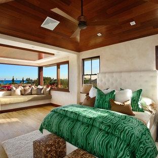 Ejemplo de dormitorio principal, exótico, extra grande, con paredes beige y suelo de madera clara