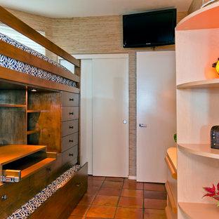 Diseño de habitación de invitados tropical, pequeña, sin chimenea, con paredes beige y suelo de baldosas de terracota