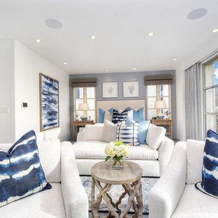 Foto di una grande camera matrimoniale stile marinaro con camino classico, pareti bianche, parquet chiaro, cornice del camino in pietra e pavimento grigio