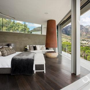 Foto de dormitorio principal, minimalista, grande, con paredes beige, suelo de madera oscura, chimenea de esquina y marco de chimenea de hormigón