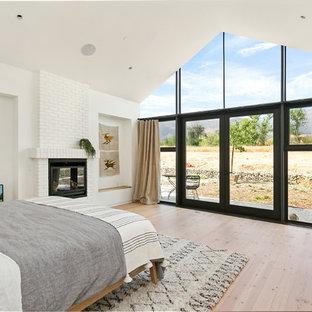 Diseño de dormitorio principal, de estilo de casa de campo, con paredes blancas, suelo de madera en tonos medios, chimenea tradicional, marco de chimenea de ladrillo y suelo marrón