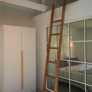 Idee per una piccola camera matrimoniale moderna con pareti bianche, pavimento in cemento, camino ad angolo, cornice del camino in intonaco e pavimento grigio