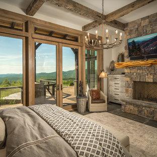Inspiration pour une chambre d'amis chalet de taille moyenne avec un mur beige, un sol en ardoise, un sol gris, une cheminée standard et un manteau de cheminée en pierre.