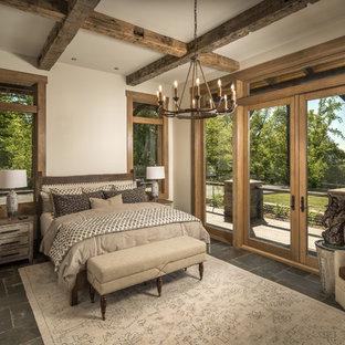 Diseño de dormitorio principal, rústico, de tamaño medio, sin chimenea, con paredes beige, suelo de pizarra y suelo gris