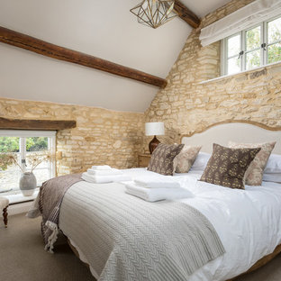 Photo of a medium sized farmhouse guest bedroom in Gloucestershire with beige walls, carpet and beige floors.