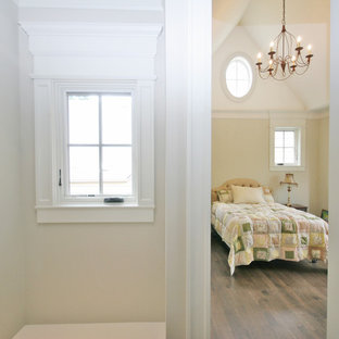Example of a mid-sized classic guest medium tone wood floor bedroom design in Chicago with beige walls