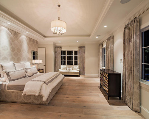 trendy master bedroom photo in miami with beige walls and light wood floors