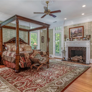 Elegant medium tone wood floor and brown floor bedroom photo in St Louis with beige walls, a standard fireplace and a stone fireplace