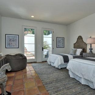 Ejemplo de habitación de invitados mediterránea, grande, sin chimenea, con paredes blancas, suelo de baldosas de terracota y suelo marrón